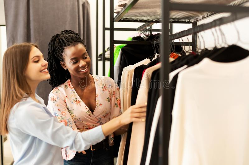 Fashion Stylist Helping Client Buy New Clothes In Clothing Store. Personal Shopper. Fashion Stylist Helping Her Client Buy New Clothes Shopping In Trendy royalty free stock photography