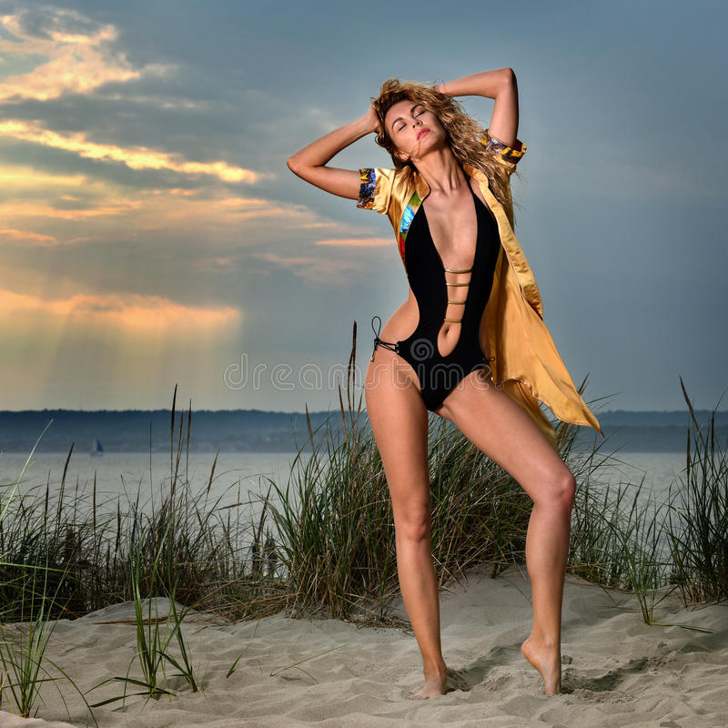 Fashion summer lifestyle photo of young woman with tanned perfect body wearing black swimsuit and shirt on the beach. royalty free stock photo