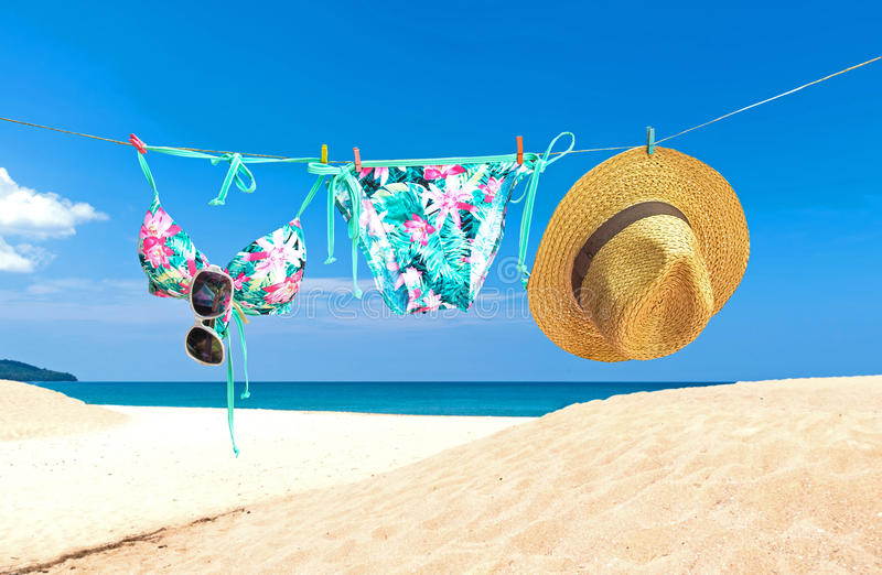 Fashion summer swimsuit bikini, sunglasses and big hat on rope. Summer bikini and accessories stylish outfit beach set. Ocean sea stock photo