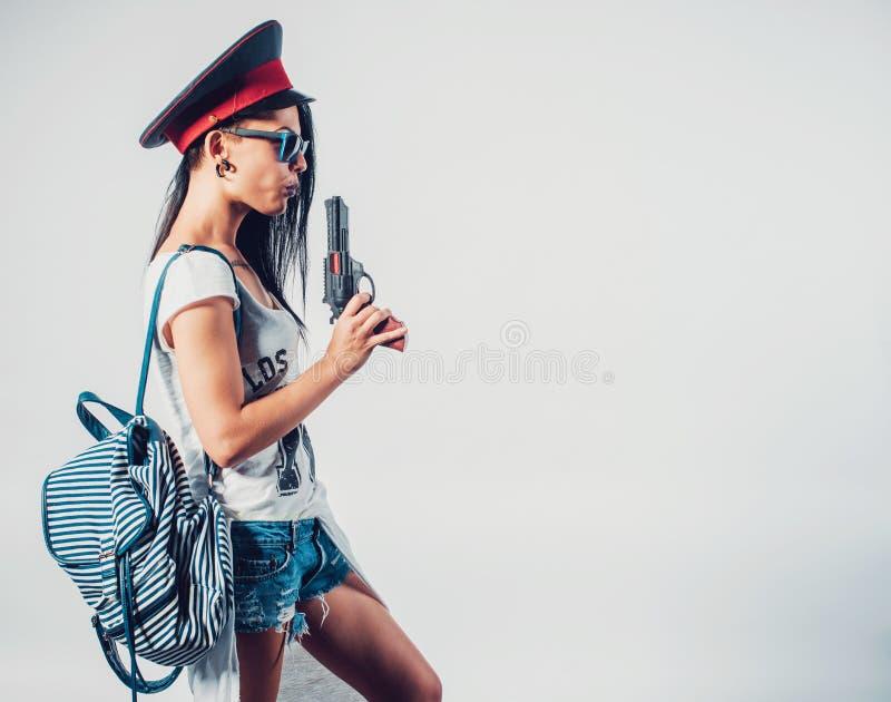 Fashion swag girl blowing on smoke toy gun. Woman having fun wearing police cap royalty free stock photo