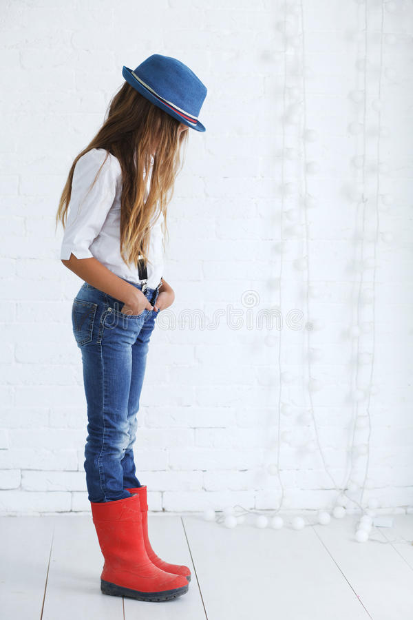 Fashion teenage girl. Cute teenage girl 8-9 years old wearing trendy hipster clothes posing over white brick wall stock images