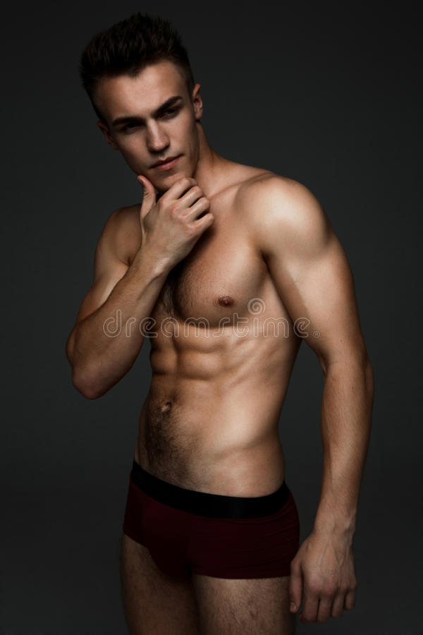 Fashion topless man. Young fashion topless man isolated on dark background royalty free stock photos