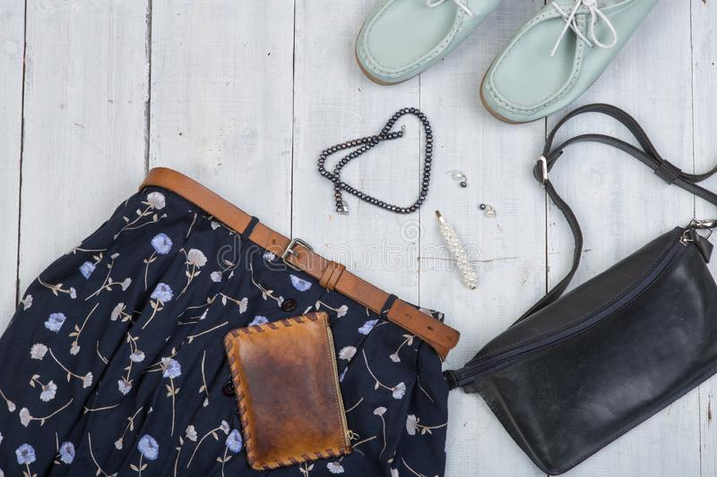 Fashion trends - blue bag, shoes and skirt in floral print, brown belt, purse and pearl jewelry. On white wooden desk, background, travel, shirt, garment royalty free stock images