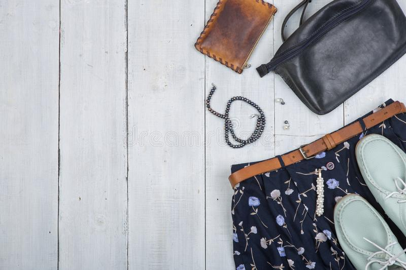 Fashion trends - blue bag, shoes and skirt in floral print, brown belt, purse and pearl jewelry. On white wooden desk, background, travel, shirt, garment stock photos