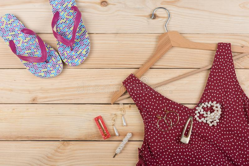 Fashion trends - flip flops, red dress in polka dots on hanger and jewelry: pearl necklace, hair pearl clip, earrings stock photography