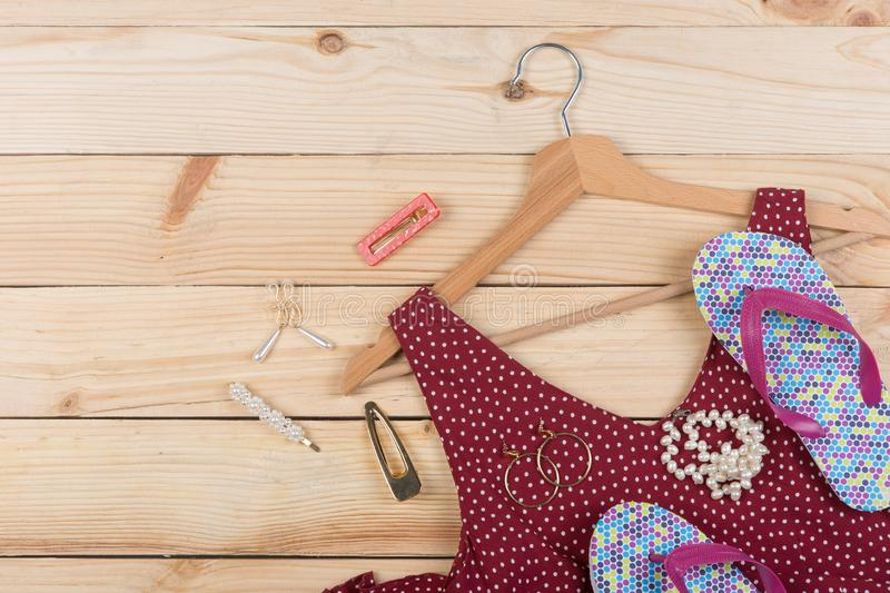 Fashion trends - flip flops, red dress in polka dots on hanger and jewelry: pearl necklace, hair pearl clip, earrings. On wooden desk, background, garment royalty free stock photos