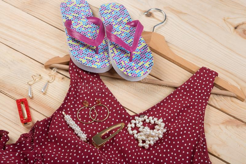 Fashion trends - flip flops, red dress in polka dots on hanger and jewelry: pearl necklace, hair pearl clip, earrings. On wooden desk, background, garment stock image