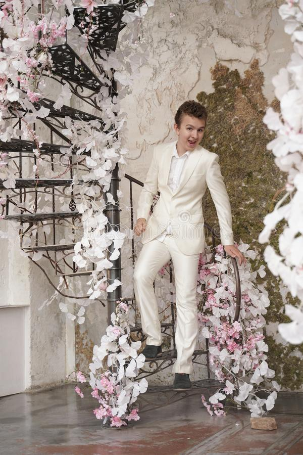 Charming handsome Caucasian young man in a white business suit, jacket and trousers, posing against a pink Sakura. Fashion trendy male teenager in stylish white stock images