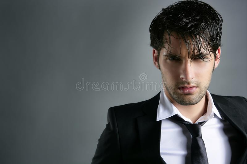 Fashion trendy suit young man hairstyle portrait. Fashion trendy suit young handsome man messy hairstyle dark portrait on gray stock photos
