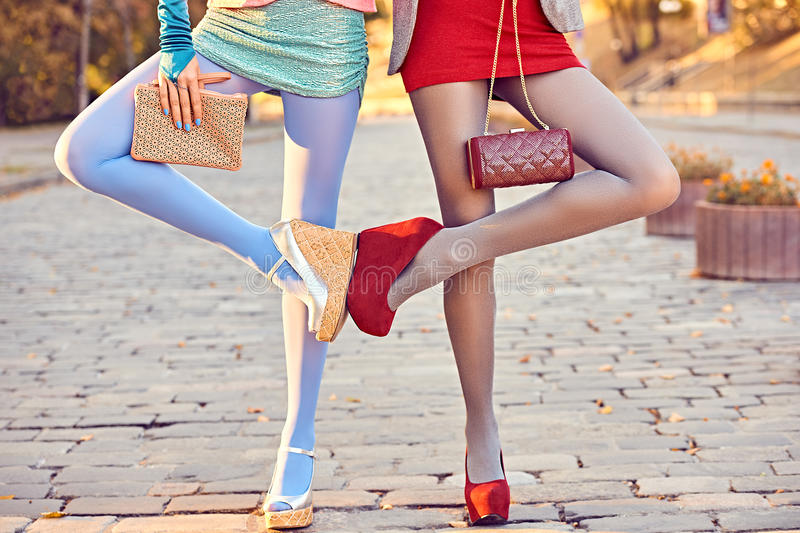 Fashion urban people, friends, outdoor. Womens on paving stone. Fashion urban beauty people, friends, outdoor. Womens legs, pantyhose, stylish shoes, clutches stock image