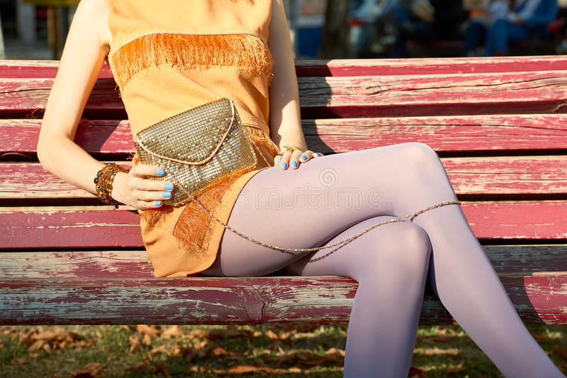 Fashion urban people, woman, outdoor. Lifestyle. Fashion urban beauty people, woman, outdoor. Playful glamor hipster girl on bench in pantyhose, stylish orange royalty free stock photography