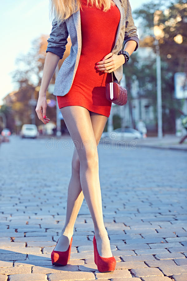 Fashion urban people, woman, outdoor. Lifestyle. Fashion urban beauty people,woman,outdoor.Playful glamor hipster girl in pantyhose.Stylish red dress,shiny royalty free stock images