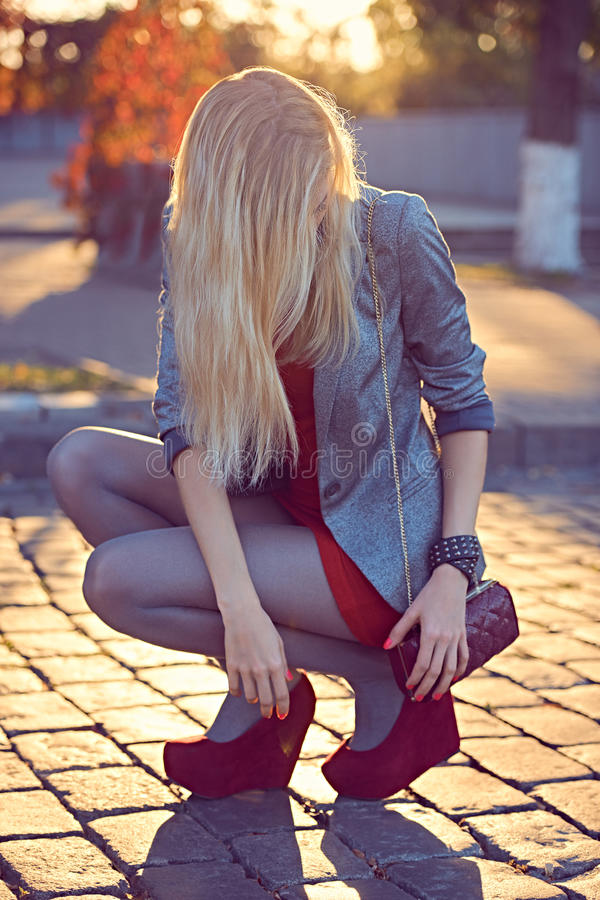 Fashion urban people, woman, outdoor. Lifestyle. Fashion urban beauty people,woman,outdoor.Playful glamor hipster girl pantyhose.Stylish red dress,shiny jacket royalty free stock images