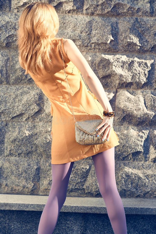 Fashion urban people, woman, outdoor. Lifestyle. Fashion urban beauty people,woman, outdoor.Playful glamor hipster redhead girl pantyhose, stylish orange dress royalty free stock images