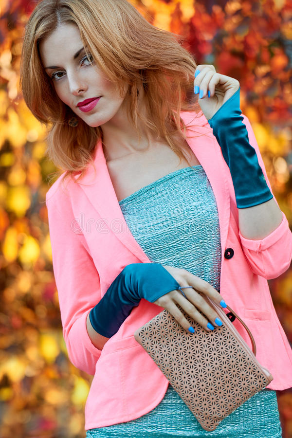 Fashion urban people, woman, outdoor. Lifestyle. Fashion urban beauty people, woman, outdoor.Playful glamor hipster redhead girl in stylish vivid jacket, gloves royalty free stock images