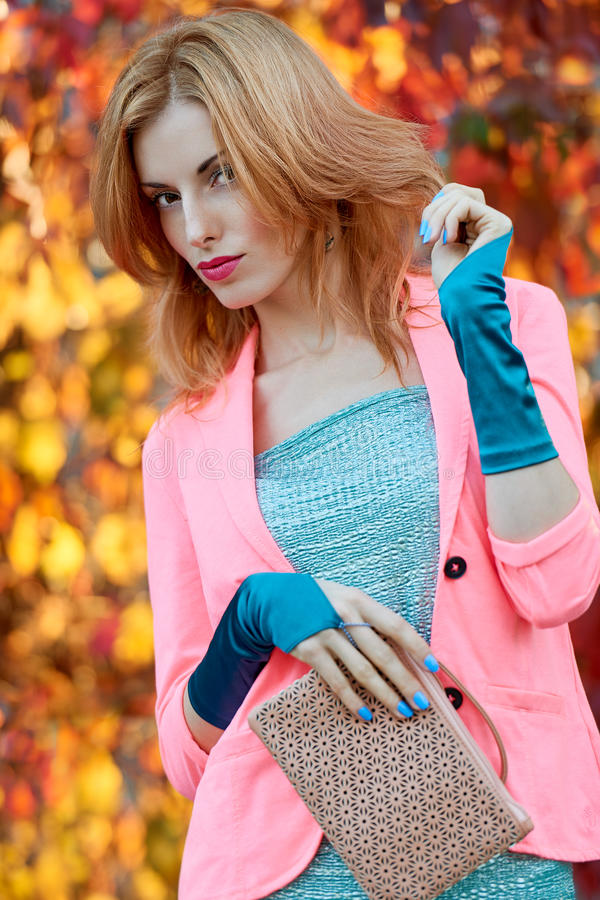 Fashion urban people, woman, outdoor. Lifestyle. Fashion urban beauty people, woman, outdoor.Playful glamor hipster redhead girl in stylish vivid jacket, gloves royalty free stock image