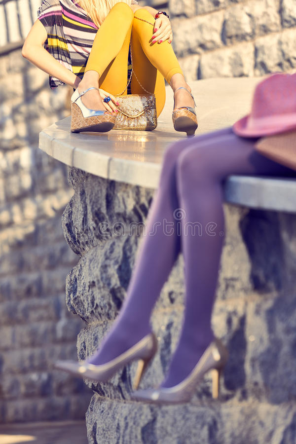 Fashion urban people, womans,outdoor. Lifestyle. Fashion urban beauty people friends,outdoor.Womens legs, pantyhose, stylish shoes, clutches.Playful hipster royalty free stock image