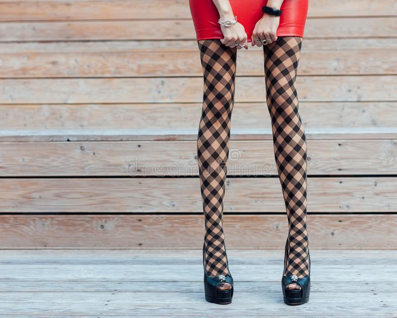 Fashion. A very girl with long legs in fashionable, fishnet stockings, a short red leather skirt and black high-heeled shoes stock image
