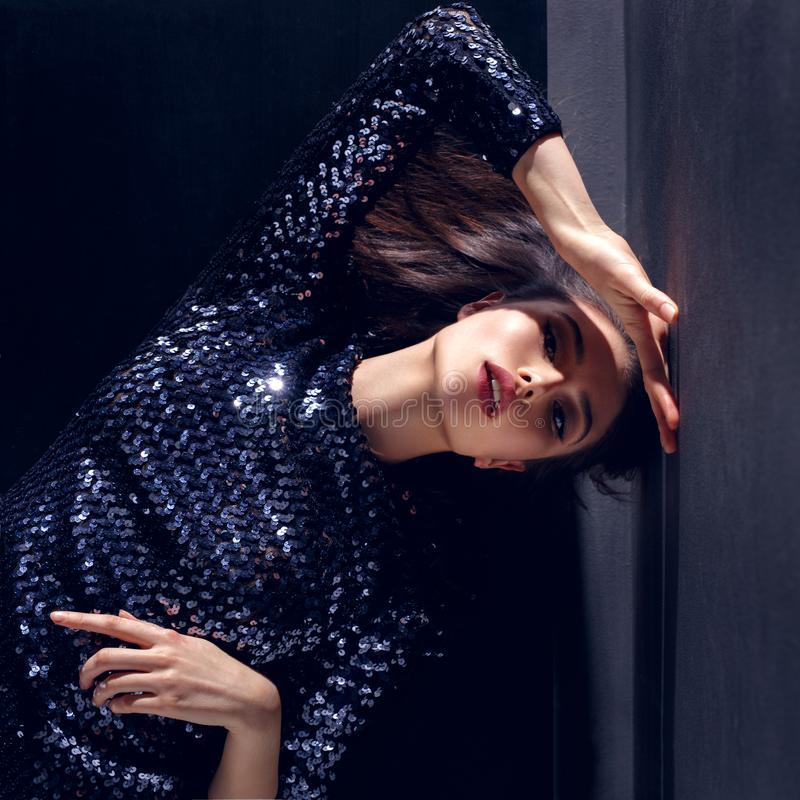Closed up of a young woman, leaning with hands, dressed in a beautiful sequins dress, isolated on a black background. stock photos