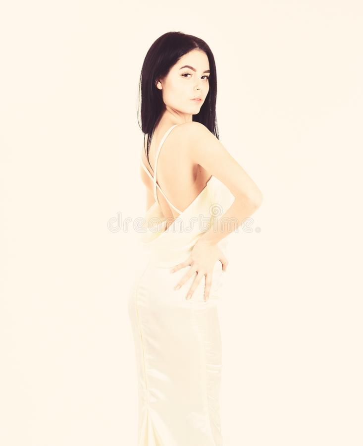 Fashion wedding concept. Woman in elegant white dress with nude back, white background. Bride, graceful girl in dress stock photography