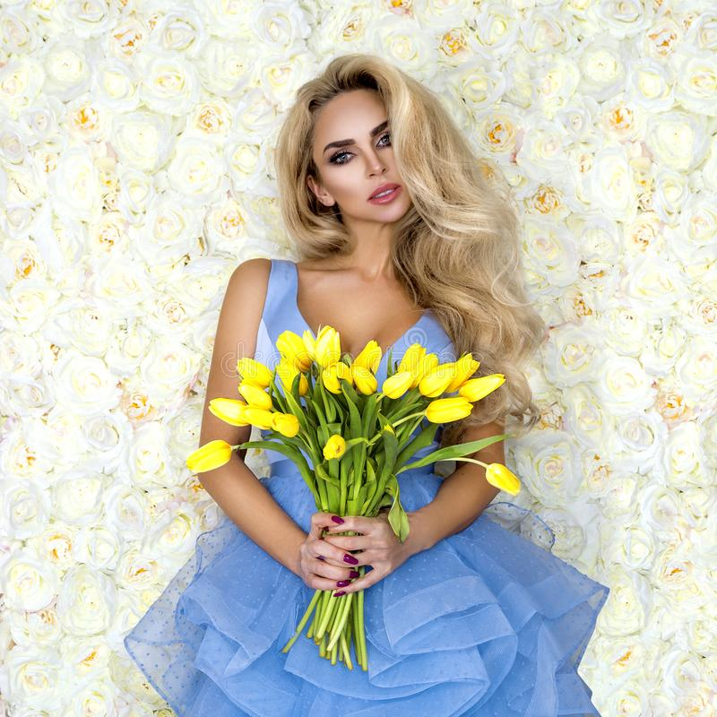 Fashion wedding dress model with a bouquet of tulips. Beautiful bride model in blue amazing wedding dress. Beauty young woman on royalty free stock photo