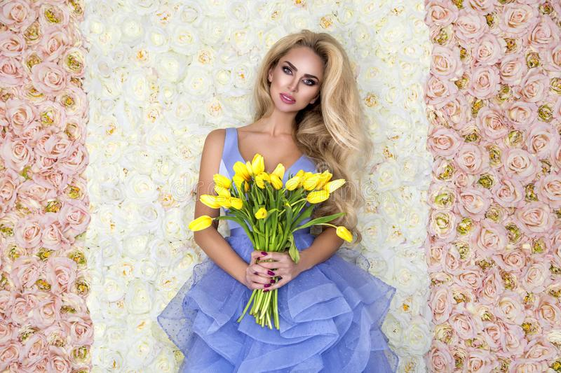 Fashion wedding dress model with a bouquet of tulips. Beautiful bride model in blue amazing wedding dress. Beauty young woman on royalty free stock photos