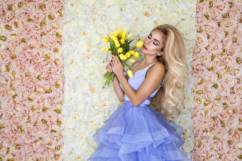 Fashion wedding dress model with a bouquet of tulips. Beautiful bride model in blue amazing wedding dress. Beauty young woman on stock photography