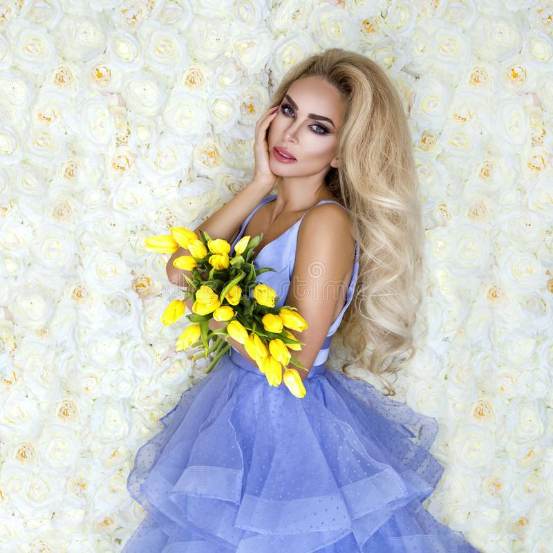 Fashion wedding dress model with a bouquet of tulips. Beautiful bride model in blue amazing wedding dress. Beauty young woman on stock images