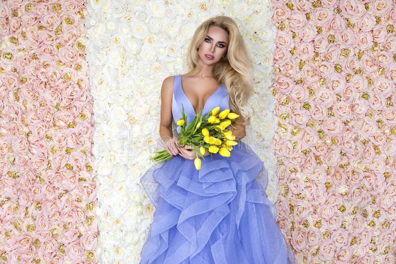 Fashion wedding dress model with a bouquet of tulips. Beautiful bride model in blue amazing wedding dress. Beauty young woman on stock image