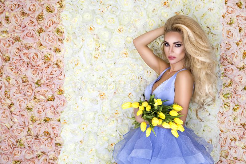 Fashion wedding dress model with a bouquet of tulips. Beautiful bride model in blue amazing wedding dress. Beauty young woman on royalty free stock photography