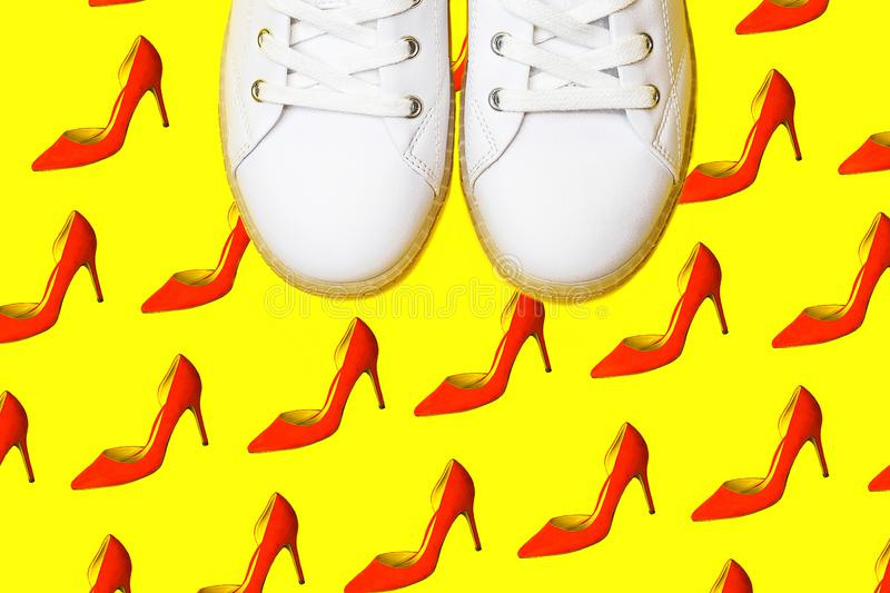 Fashion white sneakers against female red shoes pattern on bright yellow background stock photos
