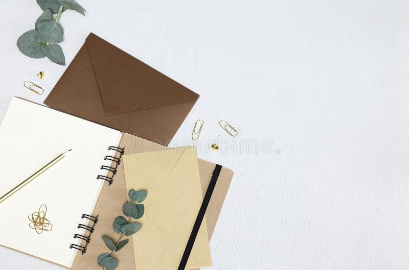 Writing a letter. Opened notebook, envelopes, golden pencil, paper clips, pins, eucalyptus branches royalty free stock photography