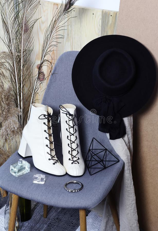 Fashion white women boots and black hat on the chair royalty free stock images