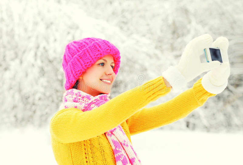 Fashion winter happy smiling young woman taking picture self portrait on smartphone over snowy trees wearing colorful knitted hat royalty free stock images