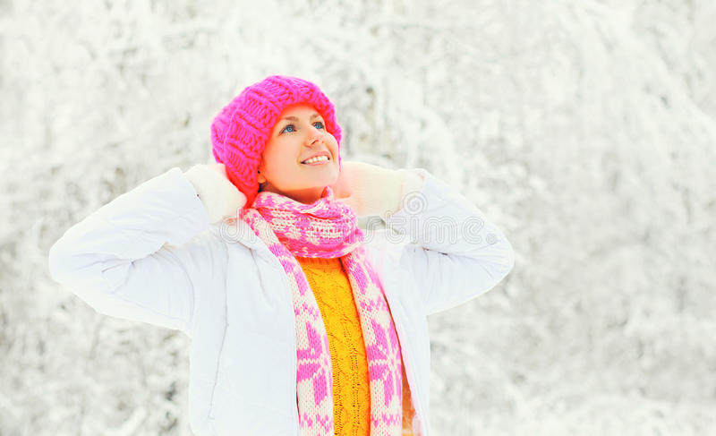 Fashion winter portrait happy woman wearing a colorful knitted hat sweater scarf over snowy background stock photography