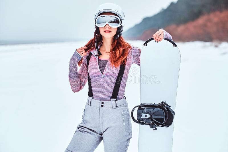 Portrait of a beautiful redhead girl in protective helmet and goggles holding a snowboard, posing on a snowy beach royalty free stock images