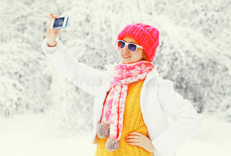 Fashion winter woman taking picture self portrait on smartphone over snowy trees wearing a colorful knitted hat scarf royalty free stock photos