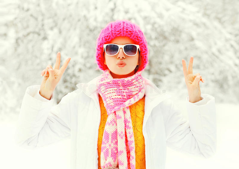 Fashion winter young woman wearing colorful knitted hat, scarf having fun over snowy forest park background stock photos