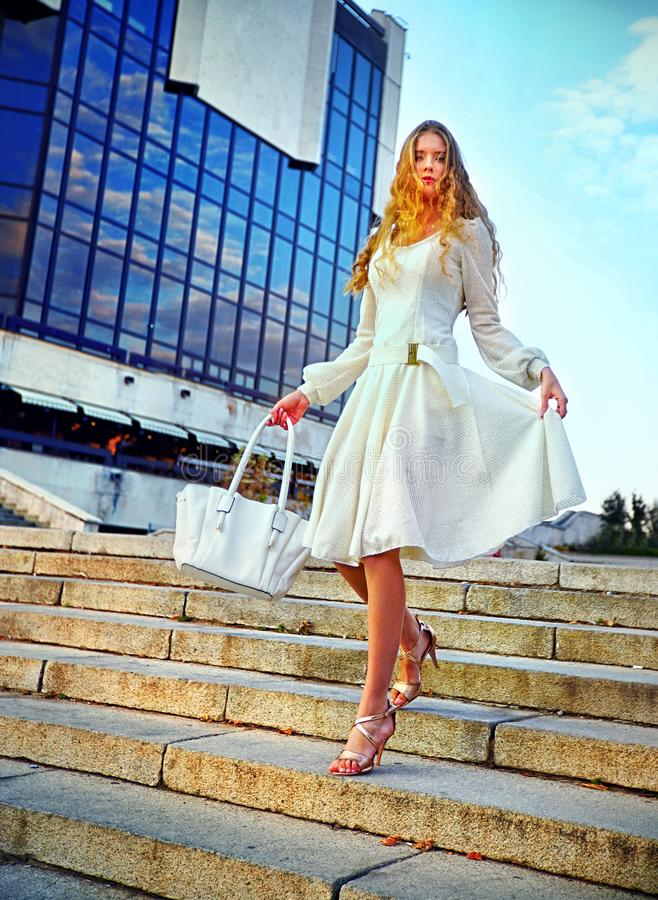 Fashion woman in autumn spring dress down stair. stock photo