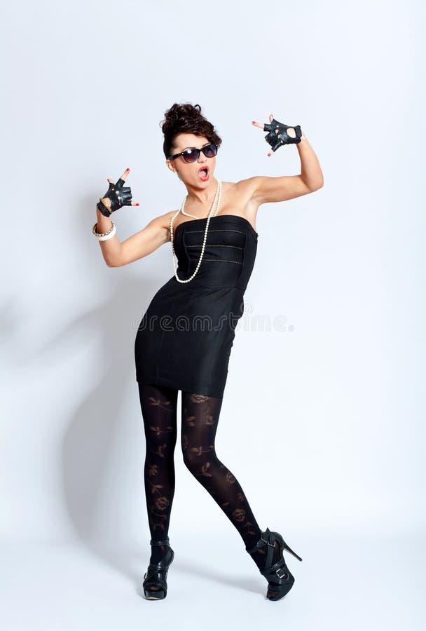 Fashion woman in black dress, making rock sign