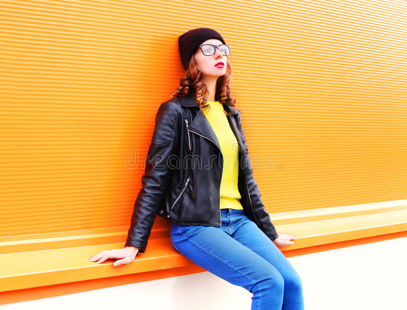 Fashion woman in black hat, rock jacket over colorful orange background. Fashion woman in black hat, rock jacket over orange colorful background stock photography