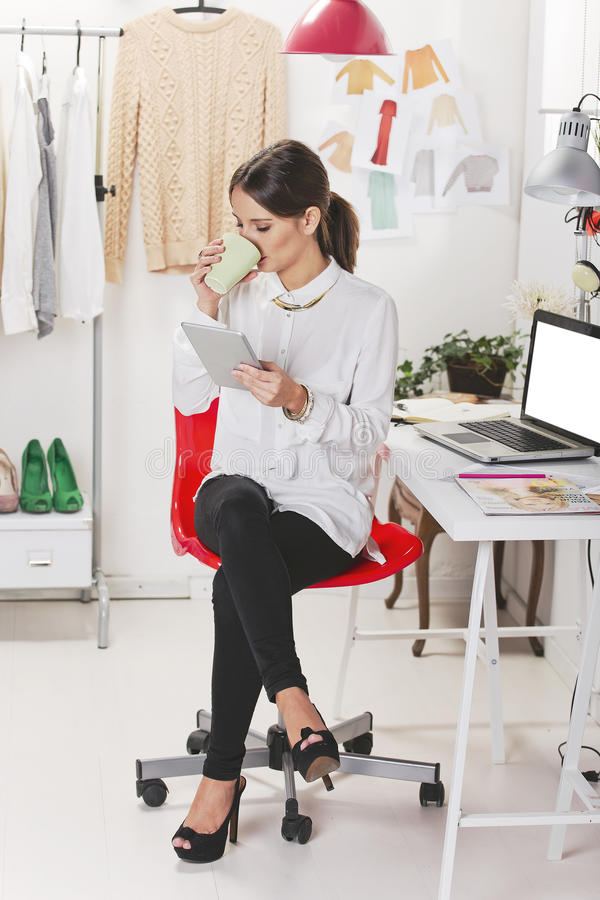 Fashion woman blogger working in a creative workspace with digit. Blogger fashion. Coffee break royalty free stock image