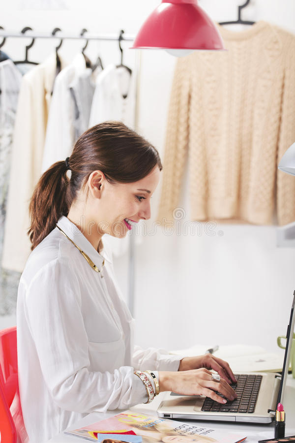 Fashion woman blogger working in a creative workspace. Young creative woman typing on a laptop in her office royalty free stock photography