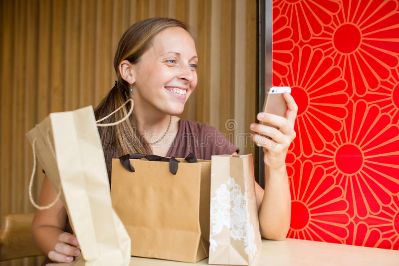 Fashion woman buying online with smart phone and credit card wit. H craft shopping bags beside royalty free stock photo