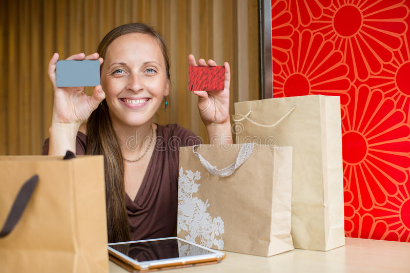Fashion woman buying online with smart phone and credit card wit. H craft shopping bags beside stock images