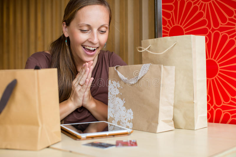 Fashion woman buying online with smart phone and credit card wit. H craft shopping bags beside stock photo