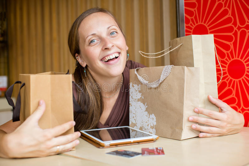 Fashion woman buying online with smart phone and credit card wit. H craft shopping bags beside royalty free stock image