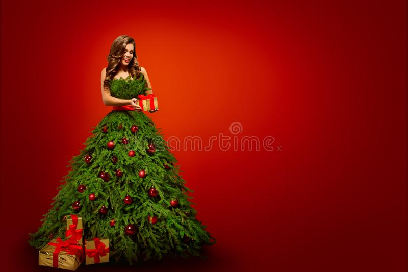 Fashion Woman in Christmas Tree Dress, Model hold Xmas Present. Gifts over New Year Red Background royalty free stock image