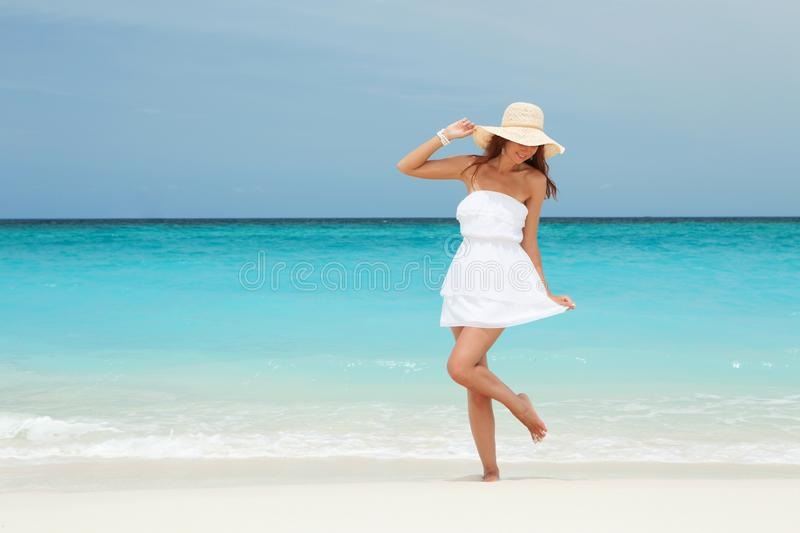 Fashion woman dancing on the beach. Happy island lifestyle. White sand, blue cloudy sky and crystal sea of tropical beach. Vacation at Paradise. Ocean beach stock photo