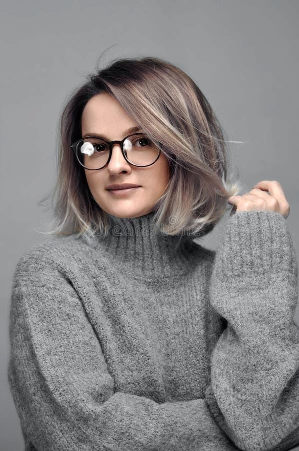 Fashion woman in eyeglasses wearing stylish grey sweater royalty free stock photography